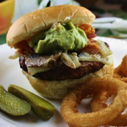 Big Bad Burgers Recipe - These burgers are packed with the flavors of horseradish, steak sauce, and Worcestershire sauce before being topped with caramelized onions and mushrooms, pepperjack cheese, bacon, and guacamole for a big and bad sandwich for which you'll be remembered.