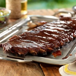 """515"" Southern-Style St. Louis Ribs Recipe - Cayenne pepper supplies the heat; brown sugar and honey in the zesty sauce provide a sweet counterbalance in these tender, southern-style grilled ribs."