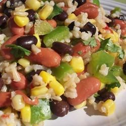 Mexican Bean and Rice Salad Recipe - Brown rice gets dressed up Mexican style, with kidney and black beans, corn, peppers, lime, and cilantro in a colorful cold salad.