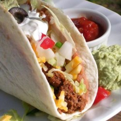 Double Decker Tacos Recipe - Like the ones you get at that famous taco place, only homemade. A soft flour tortilla, spread with refried beans, is wrapped around a crisp taco shell with seasoned meat, cheese, lettuce, tomato, onion, and guacamole.