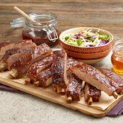 Kansas City Style St. Louis Ribs Recipe - Barbecue-seasoned St. Louis ribs are grilled slowly over low heat and brushed with Kansas City-style barbecue sauce.