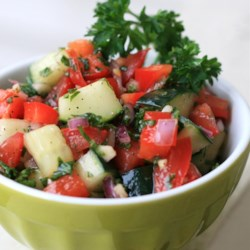 Israeli Tomato and Cucumber Salad Recipe - Chopped tomatoes, cucumbers, onions, and parsley combine with a drizzled dressing of lemon juice, olive oil, garlic, and mint leaves.