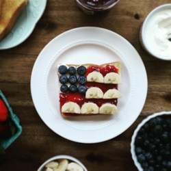 Red, White, and Blue Flag Toast Recipe - Thick slices of toast are topped with cream cheese, dotted with blueberries to stand in for the stars, with 'stripes' of bananas on a field of strawberry jam for a fun patriotic snack.