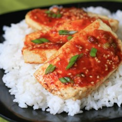 Baked Tofu Slices Recipe - Baked slices of tofu are topped with a mixture of soy sauce, chile-garlic sauce, Sriracha, and sesame seeds in this simple baked tofu recipe.