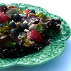 Spring Salad with Blueberry Balsamic Dressing Recipe - Celebrate spring with this refreshing green salad topped with fresh berries, blue cheese, walnuts, and a blueberry-balsamic dressing.