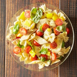 Tomato Basil Pasta Salad Recipe - Made ahead of time and kept refrigerated, this pasta salad with cherry tomatoes, yellow bell pepper, and artichoke hearts and fresh basil is a real time saver when you're expecting guests.