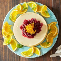 Orange Citrus Cheesecake Recipe - Creamy cheesecake flavored with bright orange zest is topped with a sauce made of fresh cranberries and orange juice.