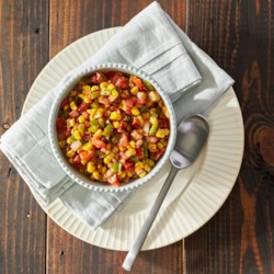 Cajun Spiced Corn Recipe - A great veggie side dish for any barbecue, spicy whole kernel corn is baked or grilled in a foil packet with onions, tomatoes, and green bell pepper.