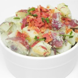 Caramelized Onion and Bacon Potato Salad Recipe - Fold tzatziki sauce and bacon into cooked red potatoes for a lighter version of potato salad. Hints of tarragon and caramelized onion add a nice dimension to every bite.