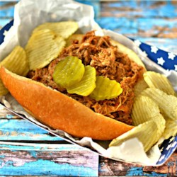 Simple Slow Cooker Pulled Pork Recipe - Succulent pulled pork slow cooked in a smokey homemade barbeque sauce makes perfect sandwiches for picnics, football Sundays, or dinner.