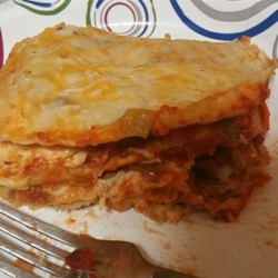 Easy Enchilada Casserole Recipe - No stuffing or rolling necessary to make these enchiladas. Just mix together shredded chicken with sour cream, jack cheese and soup, then layer with tortillas and salsa.