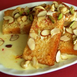 Shahi Tukra (Indian Bread Pudding) Recipe - Deep-fried bread absorbs a milk sauce seasoned with saffron and cardamom, all of which is covered by fried cashews, almonds, and pistachios in this dessert recipe from Hyderabad, India.