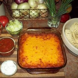 Layered Nacho Bake Recipe - Serve this hot dip made with seasoned ground beef, refried beans and cheese with crunchy tortilla chips and fresh taco-style toppings!