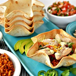 Chicken Taco Bowls with Pinto Beans and Rice Recipe - Taco bowls are filled with chicken breast strips, rice and pinto beans, pico de gallo, shredded cheese, and more for a fun weeknight dinner.