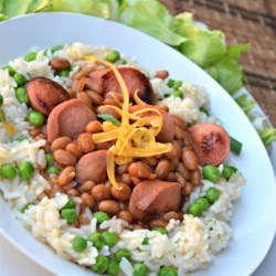 Dogs 'n' Beans Rice Bowl Recipe - Browned hot dog pieces are simmered with baked beans and served over a rice, peas, and cheese mixture for a quick and tasty weeknight dinner.