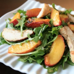 Grilled Chicken, Peach, and Arugula Salad Recipe - Chicken and fresh peaches are grilled and served on top of arugula dressed in a homemade vinaigrette in this simple grilled salad recipe.