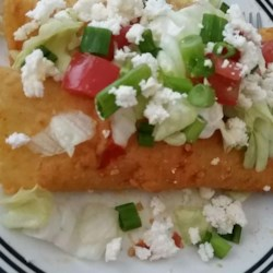 Authentic Mexican Enchiladas Recipe - This is the real thing! Corn tortillas are dipped in a home made sauce, fried, filled with Mexican queso fresco, then topped with sour cream, lettuce and tomato. My mother in law is from Mexico and taught me to make this delicious dish! Serve with authentic refried beans, it has a taste different from the norm--so good!