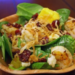 Tropical Shrimp Spinach Salad Recipe - Warm shrimp, mango, goat cheese, and toasted coconut combine in this refreshing salad.