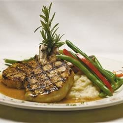 Pork Chops with Praline Sauce Recipe - Pork chops are topped with a sauce made with evaporated milk, brown sugar, and pecans in this recipe.