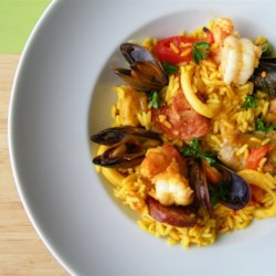 Paella I Recipe - A very traditional paella, garnished with chorizo, chicken, peas, squid, mussels, and shrimp. Spanish Chorizo is a smoked sausage with a different flavor than Mexican chorizo. A paella pan is recommended for this recipe.