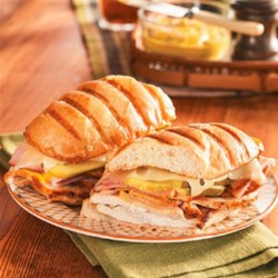 Cuban Sandwich from Smithfield(R) Recipe - Slices of roasted pork loin and ham are layered with mustard, pickles, and Swiss cheese in a hoagie roll. The sandwiches are then grilled in butter until golden brown.