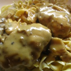 Scrumptious Salisbury Steak in Mushroom Gravy Recipe - A classic Salisbury steak in beef and mushroom gravy. This simple, hearty dish will remind you of Sunday dinners at grandma's house.  This is my husband's all-time favorite meal. The recipe makes plenty of gravy, so serve with mashed potatoes or buttered noodles.