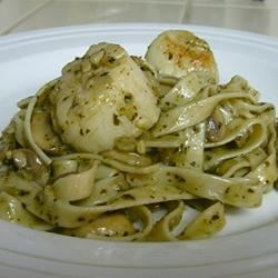 Pasta with Pesto and Scallops Recipe - A fragrant saute of onions, garlic, bell pepper and  mushrooms is simmered with white wine and lemon juice, with fresh scallops tossed in to soak up the flavors. Serve with fettucini bathed in pesto, and sprinkle with Parmesan cheese.