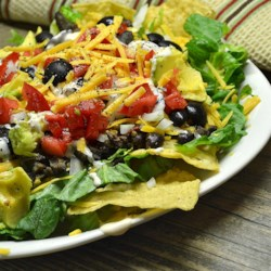 Easy Black Bean Taco Salad Recipe - Seasoned ground beef and black beans form the basis of a hearty taco salad with layers of lettuce, salsa, Mexican cheese blend, and sour cream and topped with tortilla chips.