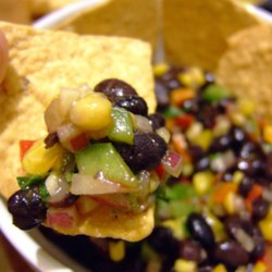 Black Bean and Corn Salsa Recipe - Canned black beans mix with yellow, orange, and green bell pepper in a simple vinegar and olive oil dressing to make this salsa.