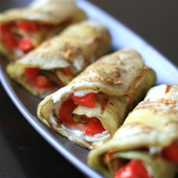 Grilled Eggplant Rollups Recipe - Grilled eggplant slices are rolled around goat cheese and roasted red peppers for a colorful summertime appetizer.