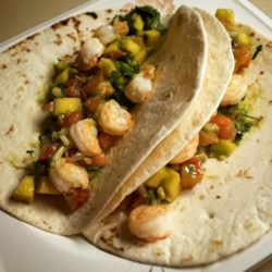 Shrimp Tacos Recipe - I got the idea for these shrimp tacos from a favorite restaurant. The shrimp is sauteed in honey butter, topped with a delicious mango salsa, and wrapped in a tortilla. It tastes worth a million bucks yet is so simple. Everyone will be begging for more.