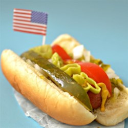 Chicago-Style Hot Dog Recipe - An all-beef hot dog on a poppy seed bun piled high with mustard, sweet pickle relish, onion, tomato, a dill pickle spear, sport peppers, and a dash of celery salt.  Don't even think about ketchup!