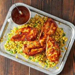 Backyard Barbecue Chicken Recipe - Chicken breasts are grilled in foil packets with corn kernels and bell pepper in a spicy barbecue sauce.