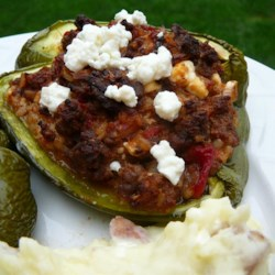 Mexican-Greek Stuffed Green Peppers Recipe - Green bell peppers stuffed with seasoned ground beef, feta cheese, and rice are a nice duo of Mexican and Greek-inspired cuisine for a weeknight dinner.
