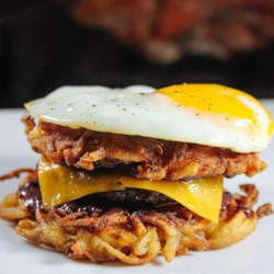 Latkes Breakfast Sandwiches with Blackberry-Yogurt Spread Recipe - Latkes, sausage, Cheddar cheese, and blackberry jam and are topped with an egg in this latke breakfast sandwich you'll need to eat with a knife and fork.