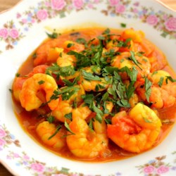 Prawns Curry Recipe - This delicious curry dish with prawns uses rice flour and turmeric to coat the prawns which are cooked in a sauce made with pureed tomatoes, onions, green chile peppers, cumin, Kashmiri red chili powder, and ginger-garlic paste.