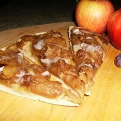 Apple Pizza Pie Recipe - For this unique recipe, a delicious dough is whipped up with butter, confectioners ' sugar and flour pressed into a pizza pan, and then baked in the oven.  Canned apple pie filling is spooned onto the crust, sprinkled with a brown sugar/cheddar cheese mixture and baked until bubbly and delicious.