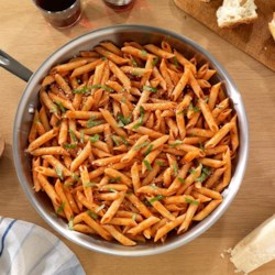 Simple Penne with Tomato & Basil Sauce Recipe - Penne pasta in a rich tomato and basil sauce is served with more fresh basil and shaved Parmigiano-Reggiano cheese.