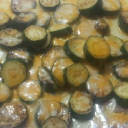 Lynda's Zucchini Recipe - Quick, easy and very good.  I always make it as an appetizer for  barbecues at home. Melted Cheddar cheese provides a wonderful, simple topping for the sauteed zucchini slices.