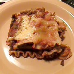 Mexican Lasagna I Recipe - Mexican seasonings and refried beans are added to this lasagna. You don't even have to pre-cook the noodles, so it is faster to prepare than traditional lasagna.