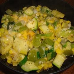 Calabacitas Recipe - Zucchini, bell pepper, onion, and corn are lightly pan-fried in olive oil and butter and topped with Monterey Jack cheese for a delightful side dish in this recipe.