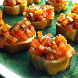 Italian-Style Bruschetta Recipe - Fresh diced tomatoes in a basil and garlic marinade top golden toast for a tasty Italian-inspired appetizer.
