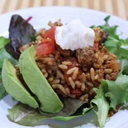 Taco Rice Bake Recipe - Taco-seasoned ground beef, flavored rice, and lots of cheese can be served with a variety of toppings in a number of ways - in taco shells, lettuce wraps, or just as is.