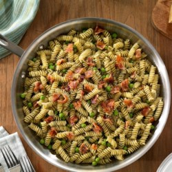 Easy One Pan Rotini with Pesto, Bacon and Peas Recipe - Rotini, pesto, green peas, and crumbled bacon make a delicious, one-skillet weeknight dinner.