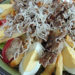 Steak 'n' Fries Salad Recipe - A salad of romaine lettuce, cucumber, and hard-cooked egg slices serves as a bed for French fries and steak in this unique salad recipe.