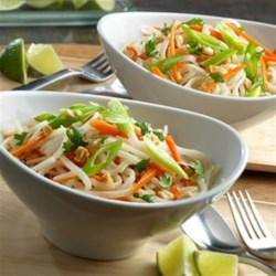 Thai Curry Noodle Bowl Recipe - 30 minutes is all it takes to make this incredibly tasty soup. Sautéed garlic, tender-crisp carrot strips and rice noodles are cooked in a ginger flavor infused broth and garnished with fresh cilantro, green onions and salted peanuts.