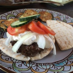 Greek Lamb-Feta Burgers With Cucumber Sauce Recipe - These grilled lamb burgers are served with slices of ripe tomatoes and red onion in pita bread with a fresh tasting cucumber sauce seasoned with fresh mint and garlic.