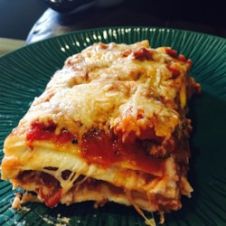 Louise's Lasagna Recipe - This lasagna gets cheesy with mozzarella cheese, cottage cheese, white American cheese, and Parmesan cheese. Adding salami and pepperoni sausage to ground beef in the tomato sauce adds yet more flavor.