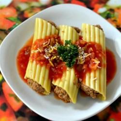 Microwave Mexican Manicotti Recipe - A family-pleasing quick dinner. Manicotti shells are filled with beef, refried beans, and seasonings, microwaved, and topped with cheese and sour cream.