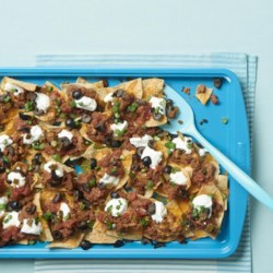 Super Nachos Recipe and Video - These are definitely super nachos with a layering of ground beef, refried beans, Cheddar cheese, olives, and more. It will be a crowd pleaser on game day.